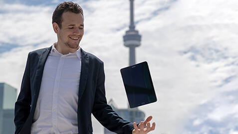 A man with a tablet with CN Tower at the back.