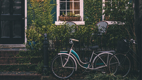 Two bicycles in front of a house.